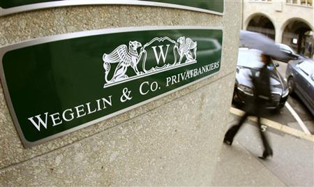The company's logo of Swiss Bank Wegelin is pictured beside the entrance of an office building in Zurich January 4, 2013. REUTERS/Arnd Wiegmann