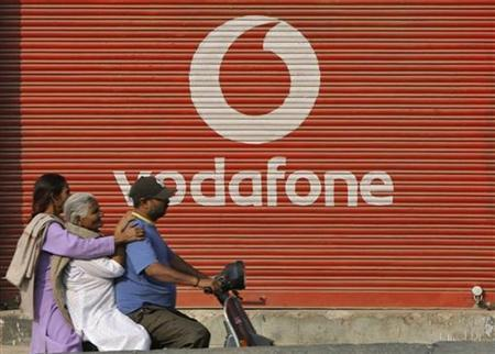 A man and two passengers ride on a scooter past a shop displaying the Vodafone logo on its shutter in Jammu November 21, 2011. REUTERS/Mukesh Gupta