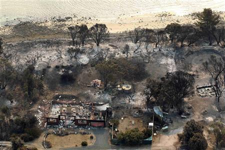 Houses destroyed by a bushfire are seen in ruins in Dunalley, about 40 kilometres (25 miles) east of Hobart, January 5, 2013. REUTERS/Chris Kidd/Pool
