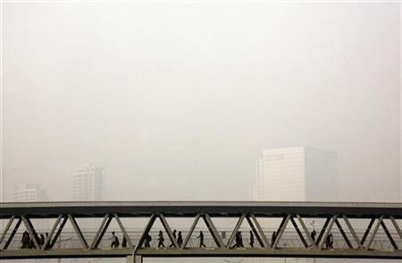 Buildings shrouded in haze behind pedestrians walking across a bridge above a main road in central Beijing October 27, 2012. REUTERS/David Gray/Files