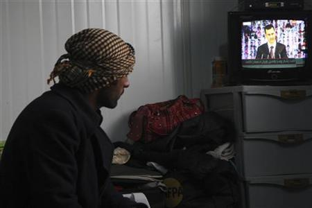 A Syrian refugee watches a television broadcast of Syria's President Bashar al-Assad speaking in Damascus, in their container at the Al-Zaatari refugee camp in the Jordanian city of Mafraq, near the border with Syria, January 6, 2013. REUTERS/Majed Jaber (JORDAN - Tags: POLITICS CIVIL UNREST)