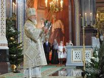 Patriarch Kirill (L) leads a Christmas service attended by Prime Minister Dmitry Medvedev (2nd L) in the Cathedral of Christ the Saviour in Moscow January 7, 2013. REUTERS/Alexander Astafyev/RIA Novosti/Pool