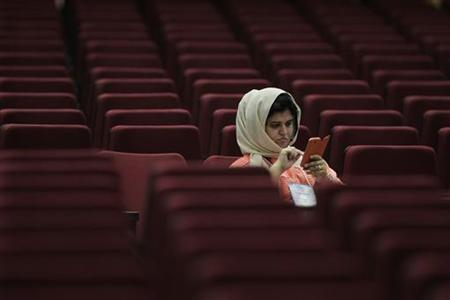 A woman uses her smartphone in an auditorium in Brasilia November 10, 2012. REUTERS/Ueslei Marcelino/Files