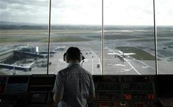 An air traffic controller monitors aircraft movement from the control tower at Manchester Airport, northern England, February 3, 2011. REUTERS/Phil Noble