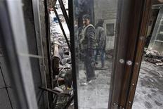 """Los combates asolaron Siria el lunes, incluso a pocos kilómetros de donde el presidente Bashar el Asad presentó el domingo su """"plan de paz"""" que los sirios de ambos bandos dijeron que no haría nada para frenar la revuelta que dura ya 21 meses. En la imagen, un rebelde del Ejército de Siria Libre carga con su arma mientras su imagen se refleja en un espejo en la ciudad vieja de Alepo, el 7 de enero de 2013. REUTERS/Muzaffar Salman"""