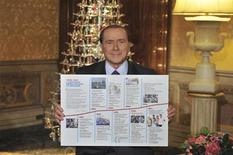 Ex-premiê italiano, Silvio Berlusconi, segura cartaz que destaca as ações tomadas por seu governo de 2001 a 2011, em sua casa, em Roma. 22/12/2012 REUTERS/Assessoria de imprensa do partido Liberdade do Povo/Divulgação
