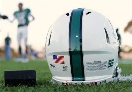 A football helmet's health warning sticker is pictured as the Oceanside Pirates high school football team prepares for their Friday night game in Oceanside, California in this file photo taken September 14, 2012. The Institute of Medicine is launching a study into sports-related concussions among youths from elementary school to early adulthood. REUTERS/Mike Blake/Files