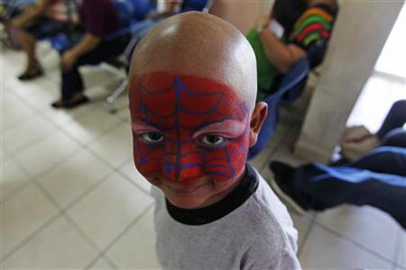 A boy suffering from cancer smiles with his face painted to resemble Spiderman during an event at the paediatric cancer section of the La Mascota children's hospital in Managua December 18, 2012. REUTERS/Oswaldo Rivas