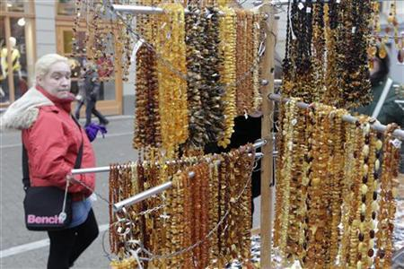 A woman passes a shop selling amber jewellery in Riga January 3, 2013. REUTERS/Ints Kalnins/Files