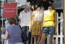 Mulher caminha diante de loja de roupas no Rio de Janeiro, em novembro de 2012. A atividade varejista no Brasil encerrou 2012 com crescimento acumulado de 6,4 por cento, o menor ritmo de expansão dos últimos três anos, informou a Serasa Experian.Setores que menos cresceram em 2012 foram o de tecidos, vestuário, calçados e acessórios e o de combustíveis e lubrificantes. 30/11/2012 REUTERS/Sergio Moraes