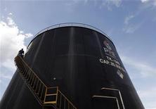 Imagen de archivo de un empleado de Pacific Rubiales subiendo las escaleras de un estanque de petróleo en Campo Rubiales en Meta, Colombia, abr 21 2010. La petrolera canadiense Pacific Rubiales anunció el martes que invertirá 1.700 millones de dólares este año y que apunta a lograr un aumento de su producción de entre un 15 a un 30 por ciento. REUTERS/Jose Miguel Gomez