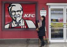 A woman walks past a KFC restaurant in Wuhan, Hubei province in this December 18, 2012 file photograph. REUTERS/Stringer/Files