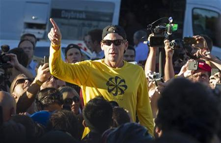 Lance Armstrong speaks to the crowd prior to a run with his fans at Mount Royal park in Montreal August 29, 2012. REUTERS/Christinne Muschi/Files
