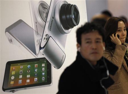 People walk past an advertisement board featuring Samsung Electronics in Seoul January 7, 2013. REUTERS/Kim Hong-Ji