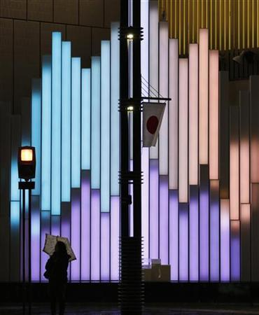 A woman holding an umbrella stands near a Japan flag in front of an illuminated display at a shopping district in Tokyo December 28, 2012. Japan's core consumer prices fell 0.1 percent in November from a year earlier, government data showed on Friday, in a sign of the persistent deflation that Japan's new prime minister has pledged to conquer with aggressive fiscal and monetary policy. REUTERS/Kim Kyung-Hoon (JAPAN - Tags: BUSINESS POLITICS TPX IMAGES OF THE DAY)