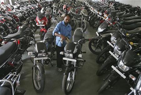 A worker cleans a Hero Splendor motorcycle at a Hero MotoCorp showroom in Jammu October 23, 2012. REUTERS/Mukesh Gupta/Files