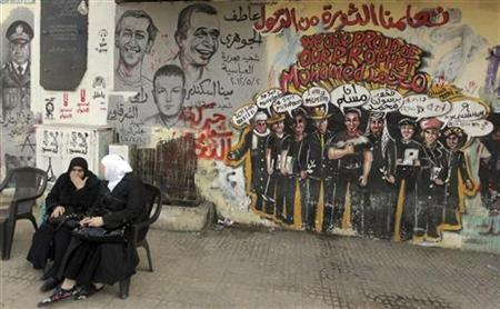 Women sit in front graffiti along Mohamed Mahmoud street near Tahrir Square in Cairo, December 30, 2012. REUTERS/Amr Abdallah Dalsh