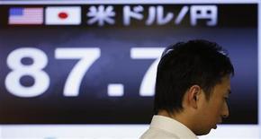Работник валютной трейдинговой компании стоит рядом с электронным табло, отражающим курс доллара США к японской иене, в Токио 4 января 2013 года. Доллар растет к иене после спада в начале недели, который привлек новых покупателей. REUTERS/Toru Hanai