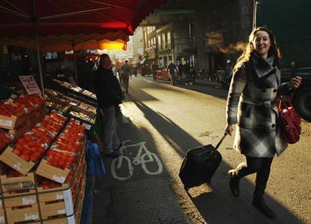 A woman walks through Borough Market in London December 9, 2011. REUTERS/Luke MacGregor