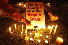 Manifestante em Cingapura acende velas próximas a um cartaz durante protesto em apoio a uma mulher vítima de estupro na Índia. Três dos homens acusados de participação no estupro e morte de uma estudante indiana em dezembro vão se declarar inocentes, disseram seus advogados nesta quarta-feira, citando lapsos na investigação policial. 02/01/2013 REUTERS/Edgar Su