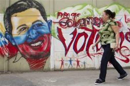 A woman walks past a mural depicting Venezuelan President Hugo Chavez in Caracas January 9, 2013. REUTERS/Carlos Garcia Rawlins