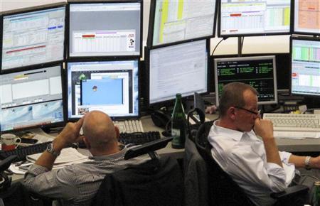 Traders are pictured at their desks at the Frankfurt stock exchange September 27, 2010. REUTERS/Remote/Pawel Kopczynski