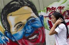 Una joven pasa junto a un mural alusivo a la figura del presidente venezolano, Hugo Chávez, en Caracas, ene 9 2013. La calificación de deuda soberana de Venezuela, ya en categoría de basura, está frente al riesgo de ser revisada en el corto plazo ante cualquier transición política dada la incapacidad del presidente Hugo Chávez de asistir a su toma de posesión el 10 de enero, advirtió el miércoles Moody's Investors Service. REUTERS/Carlos Garcia Rawlins