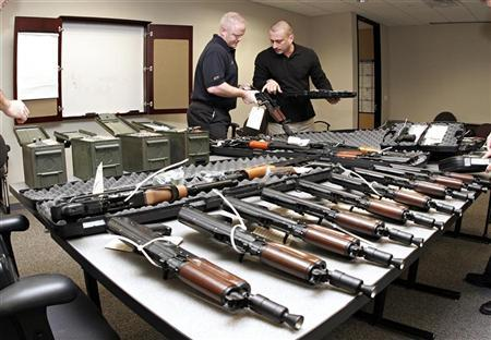 Phoenix Bureau of Alcohol, Tobacco, Firearms & Explosives (ATF) special agents Tom Mangan (L) and Peter Forcelli examine a confiscated AK-47 short pistol at the bureau's headquarters in Phoenix, Arizona January 14, 2008. REUTERS/Jeff Topping