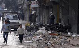 Boys walk past a car damaged by shelling in the al-Mashhad district of Aleppo January 9, 2013. REUTERS/Zain Karam