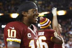Washington Redskins quarterback Robert Griffin III (10) smiles on the sideline as time runs out in his team's victory over the Dallas Cowboys at the end of their NFL football game in Landover, Maryland, December 30, 2012. REUTERS/Jonathan Ernst