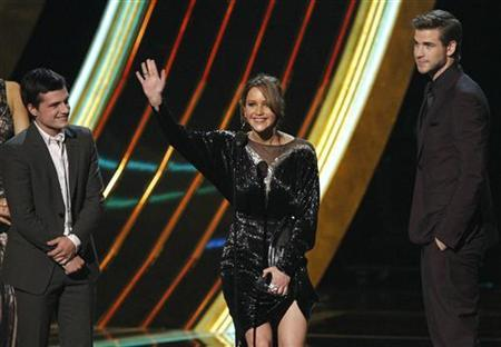 Cast members for the ''Hunger Games'' Josh Hutcherson (L), Jennifer Lawrence, and Liam Hemsworth react after accepting the award for ''Favorite Movie'' at the 2013 People's Choice Awards in Los Angeles, January 9, 2013. REUTERS/Mario Anzuoni