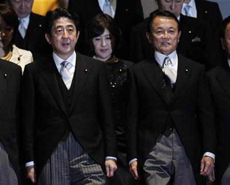 New Japanese Prime Minister Shinzo Abe (L) prepares for a photo session with Finance Minister Taro Aso and other ministers after their first cabinet meeting at Abe's official residence in Tokyo December 26, 2012. REUTERS/Yuya Shino/Files