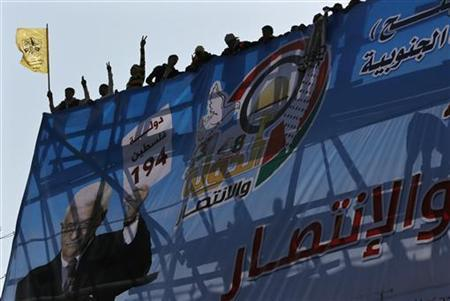 Palestinians stand behind a poster depicting Palestinian President Mahmoud Abbas during a rally marking the 48th anniversary of the founding of the Fatah movement, in Gaza City January 4, 2013. REUTERS/Suhaib Salem