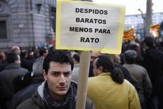 Los sindicatos CCOO y UGT han criticado la contratación de Rodrigo Rato, ex presidente de la nacionalizada Bankia, como asesor para Telefónica al considerar que perjudica la imagen de la empresa. En la imagen, varios trabajadores protestan por los recortes en Bankia con un cartel que hace referencia a Rato el 9 de enero de 2013 en Barcelona. REUTERS/Gustau Nacarino