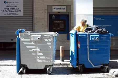 A man searches for food inside a garbage container, in front of a bank in central Athens June 24, 2012. REUTERS/Pascal Rossignol/Files