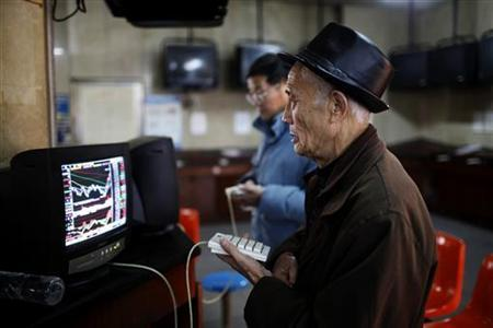 An investor looks at a computer screen showing stock information at a brokerage house in Shanghai January 4, 2013. REUTER/Aly Song