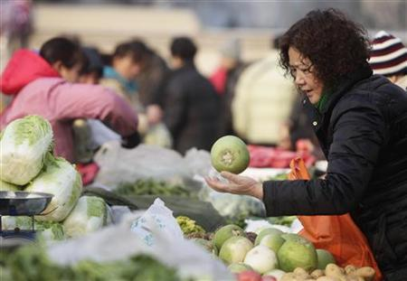 A woman selects aturnip at a morning market in central Beijing February 15, 2011. REUTERS/Jason Lee/Files