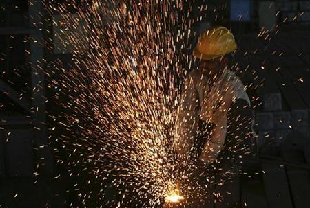 A worker cuts steel bars inside a factory on the outskirts of Hyderabad August 12, 2011. REUTERS/Krishnendu Halder/Files