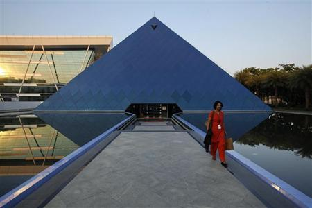 An employee walks out of an iconic pyramid-shaped building made out of glass in the Infosys campus at Electronics City in Bangalore, February 28, 2012. REUTERS/Vivek Prakash/Files