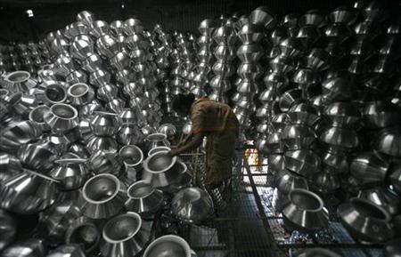 A worker checks aluminium utensils inside a factory on the outskirts of Agartala, October 12, 2012. REUTERS/Jayanta Dey/Files