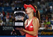 Agnieszka Radwanska of Poland kisses the trophy after defeating Dominika Cibulkova of Slovakia during their women's final match at the Sydney International tennis tournament January 11, 2013. REUTERS/Daniel Munoz