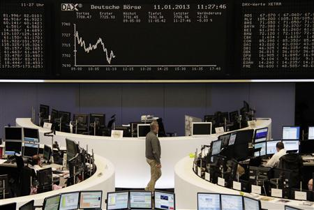 Traders are pictured at their desks in front of the DAX board at the Frankfurt stock exchange January 11, 2013. REUTERS/Remote/Lizza David