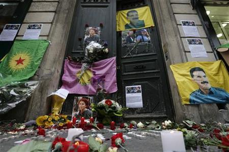 Flags, flowers and candles displayed by members of the Kurdish community are seen in front of the entrance of the Information Centre of Kurdistan in Paris, where three Kurdish women were found shot dead, January 11, 2013. REUTERS/Christian Hartmann (FRANCE - Tags: POLITICS CRIME LAW)
