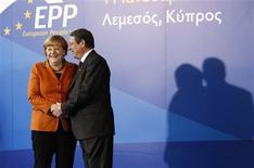 La chancelière allemande Angela Merkel aux côtés du dirigeant de l'opposition chypriote Nicos Anastasiades, donné favori de l'élection présidentielle prévue le 17 février, à l'occasion d'une réunion des partis de centre-droit européens à Limassol. Chypre mise plus que jamais sur l'obtention d'une aide internationale qui semblait encore loin d'être acquise vendredi après la dégradation brutale de la note de crédit de Moody's. /Photo prise le 11 janvier 2012/REUTERS/Jamal Saidi