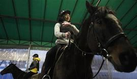 A 14-year old girl, who preferred to be identified only by her surname, Kim, rides a horse at Riding Healing Center in Incheon, west of Seoul December 26, 2012. REUTERS/Kim Hong-Ji