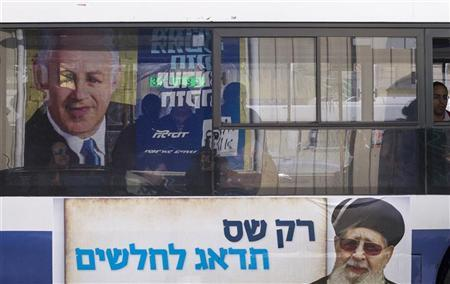 Passengers ride a bus with a Shas campaign advertisement, depicting the party's spiritual leader Rabbi Ovadia Yosef (bottom), and with a reflection on the window of a campaign poster depicting Israel's Prime Minister Benjamin Netanyahu in Bnei Brak near Tel Aviv January 7, 2013. REUTERS/Baz Ratner