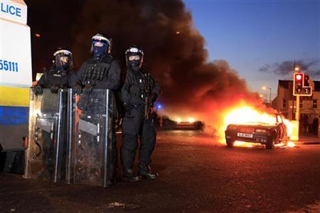 Police officers in riot gear stand near a burning hijacked car during rioting in East Belfast, January 12, 2013. Violent protests continue in Northern Ireland as loyalists renewed their anger against restrictions on flying the union flag from Belfast City Hall. REUTERS/Cathal McNaughton (NORTHERN IRELAND - Tags: CIVIL UNREST POLITICS TPX IMAGES OF THE DAY)