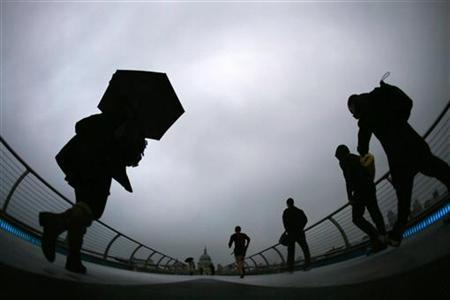 Commuters cross the Millenium Bridge during a rainy morning, towards the financial district the City of London November 27, 2012. REUTERS/Stefan Wermuth