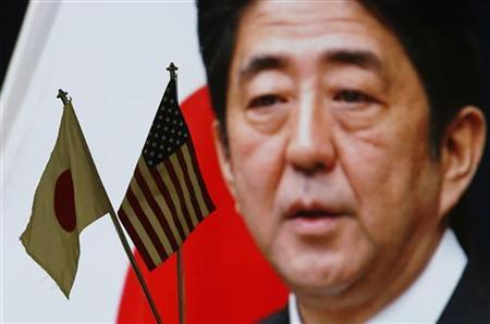 Japan and U.S. national flags are seen in front of a television screen showing Japan's Prime Minister Shinzo Abe speaking at a news conference at a foreign exchange trading company in Tokyo January 11, 2013. REUTERS/Toru Hanai