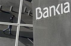 Мужчина отражается в окне штаб-квартиры испанского банка Bankia в Мадриде 28 ноября 2012 года. Проблемным странам еврозоны, ищущим поддержки у фонда помощи региона, чтобы избежать обвала банков, придется разделить с ним бремя расходов, говорится в проекте предложения, о котором пишет газета Financial Times. REUTERS/Andrea Comas